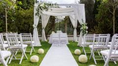 Setup of an outdoor wedding ceremony with white chairs.